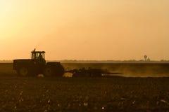 Silhouet van landbouwer die zijn land na de oogst bewerkt. Royalty-vrije Stock Fotografie