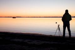 Silhouet van lange aardfotograaf bij driepoot die beeld op strand nemen bij zonsondergang royalty-vrije stock afbeeldingen