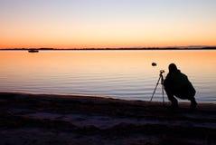Silhouet van lange aardfotograaf bij driepoot die beeld op strand nemen bij zonsondergang stock afbeeldingen