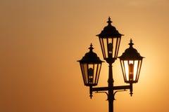 Silhouet van lantaarn tegen het toenemen zon Stock Foto's