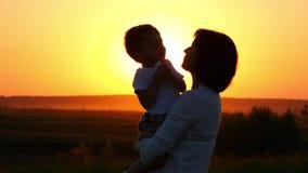 Silhouet van mamma en haar baby bij zonsondergang stock footage
