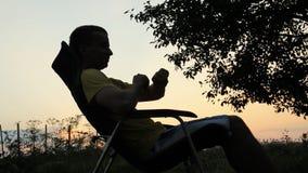 Silhouet van mannetje als voorzitter met smartwatch Tegen de achtergrond van een oranje hemel na zonsondergang stock video