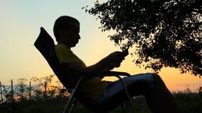 Silhouet van mannetje in stoel het spelen in tablet Tegen de achtergrond van een oranje hemel na zonsondergang stock videobeelden