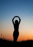 Silhouet van meisje het springen op gebied Stock Foto's