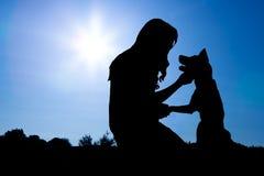 Silhouet van Meisje met Hond in Ochtendzonsopgang Stock Foto