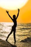Silhouet van meisje met opgeheven handen op het strand bij zonsondergang stock fotografie
