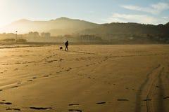 Silhouet van mens en hond die op een zandig strand door de Atlantische Oceaan de lopen Stock Foto's