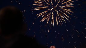 Silhouet van mens het letten op exploderend vuurwerk ter ere van de vakantie Feest begroeting stock footage