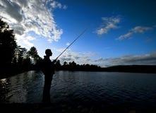 Silhouet van mens visserij stock foto