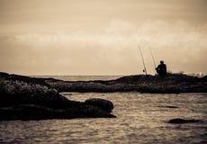 Silhouet van mensen die door het overzees vissen Stock Foto