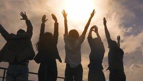 Silhouet van mensen die en zich zijn handen verheugen opheffen een groep succesvolle gelukkige zakenlieden en viert stock video