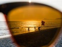 Silhouet van mensen die op het strand tijdens zonsondergang, achter zon lopen royalty-vrije stock foto