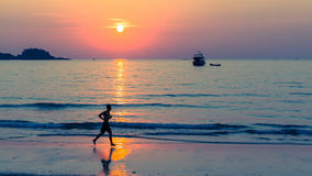 Silhouet van mensen die op kust lopen Stock Afbeelding
