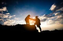Silhouet van mensen die persoon op de berg helpen bij ochtend royalty-vrije stock afbeeldingen