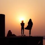Silhouet van mensen die yoga uitoefenen Stock Fotografie
