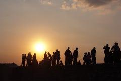 Silhouet van mensen op een zonsondergangachtergrond Stock Foto's