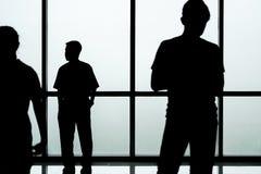 Silhouet van mensen voor de achtergrond van de glasmuur, abstract beeld Stock Afbeelding