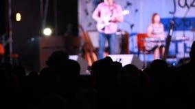 Silhouet van mensen voor heldere scène met muziekband stock videobeelden