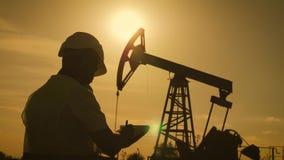 Silhouet van menseningenieur met klembord en effecten voor de olie pompende eenheid die op de plaats van ruwe olie toezicht houde stock footage