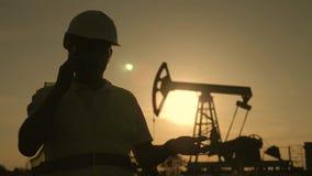 Silhouet van menseningenieur met telefoon die op de plaats van ruwe olieproductie toezicht houden bij zonsondergang stock videobeelden