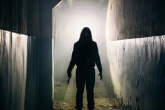 Silhouet van mensenmaniak of moordenaar of verschrikkingsmoordenaar met mes in hand in donkere griezelige en griezelige gang royalty-vrije stock foto