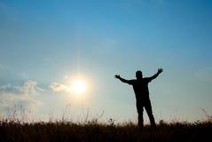 Silhouet van mensenverering met handen aan de hemel in aard wordt opgeheven die Stock Fotografie