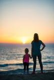 Silhouet van moeder en babymeisje op strand Royalty-vrije Stock Foto