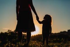Silhouet van moeder en dochterholdingshanden bij zonsondergang stock foto's
