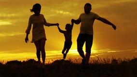 Silhouet van moeder en vader de hand van de holdingsbaby en het springen bij zonsondergang stock videobeelden