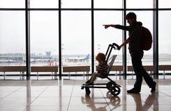Silhouet van moeder met haar peuterzoon in wandelwagen tegen het venster bij de luchthaven Het mamma richt de richting met haar v royalty-vrije stock foto's