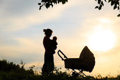 Silhouet van moeder met weinig baby en wandelwagen bij hemel stock afbeelding