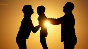 Silhouet van moedervader en kind De vader gaat het kind tot de moeder over Het concept een gelukkige familie stock videobeelden