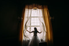 Silhouet van mooie bruid vooraan venster stock foto