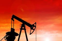 Silhouet van oliepomp bij zonsondergang Stock Afbeelding