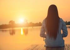 Silhouet van ontspannende jonge vrouw op houten pijler bij het meer in zonsondergang Royalty-vrije Stock Afbeeldingen