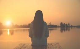 Silhouet van ontspannende jonge vrouw op houten pijler bij het meer in zonsondergang Royalty-vrije Stock Foto