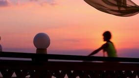 Silhouet van paar die op strand bij zonsondergang lopen stock videobeelden