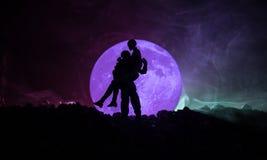 Silhouet van paar het kussen onder volle maan Het meisjeshand van de kerelkus op de achtergrond van het volle maansilhouet Het co Stock Fotografie