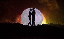 Silhouet van paar het kussen onder volle maan Het meisjeshand van de kerelkus op de achtergrond van het volle maansilhouet Het co Stock Foto's