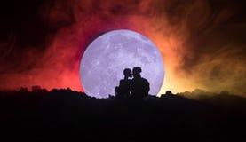 Silhouet van paar het kussen onder volle maan Het meisjeshand van de kerelkus op de achtergrond van het volle maansilhouet Het co Stock Afbeelding