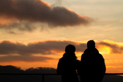 Silhouet van paar het letten op zonsondergang Stock Foto's