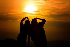 Silhouet van paar in liefde die op een zonsondergang op de bergen letten, stock foto