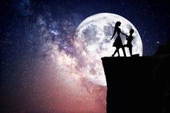 Silhouet van paar met sterrige nachthemel en maan stock afbeeldingen