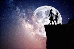Silhouet van paar met sterrige nachthemel en maan stock fotografie