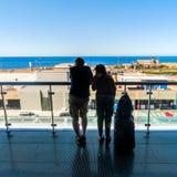 Silhouet van passagiers die op open terras in luchthaven wachten Stock Foto's