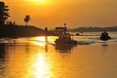 Silhouet van pier en veerboot in oranje zonlicht Royalty-vrije Stock Foto