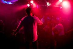 Silhouet van presentator met microfoon in hand op stadium bij overleg in nachtclub stock afbeelding