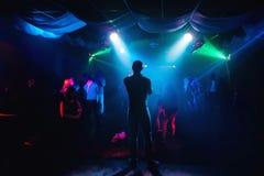 Silhouet van presentator op stadium bij overleg in nachtclub royalty-vrije stock afbeeldingen