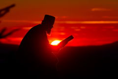 Silhouet van priesterlezing in het zonsonderganglicht, Roemenië Stock Foto's