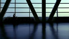 Silhouet van reizigerspassagiers in de terminal die van de luchthavendoorgang met bagagebagage het gaande reizen lopen stock videobeelden